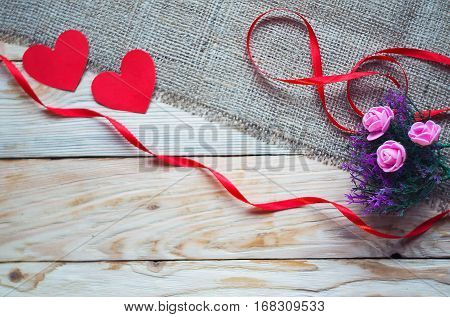 Red ribbon and heart on a wooden background