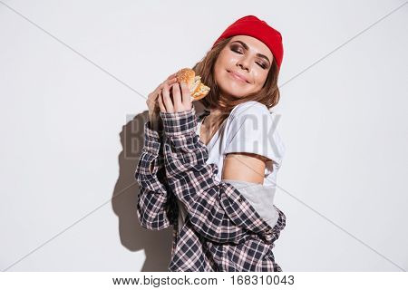 Photo of hungry lady dressed in shirt in a cage print wearing hat standing isolated over white background and eating burger