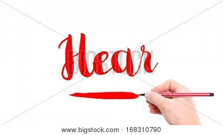 The verb hear written on a white background