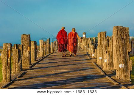 buddhist monks walking at U Bein Bridge Taungthaman Lake Amarapura Mandalay state Myanmar