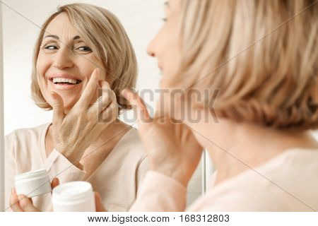 Senior woman applying cosmetic cream on face near mirror