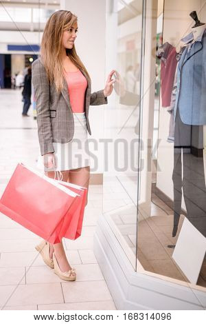 Portrait of beautiful woman window shopping in mall