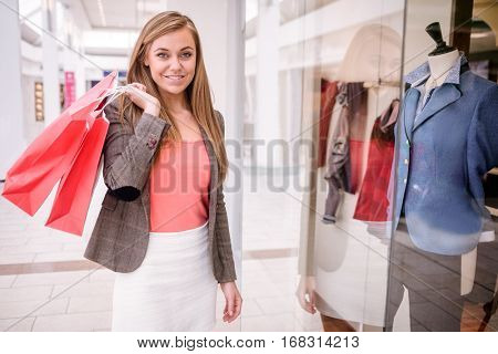 Portrait of smiling woman holding shopping bags while shopping in mall