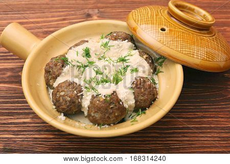 Meatballs with sauce cream in ceramic frying pan on a wooden background
