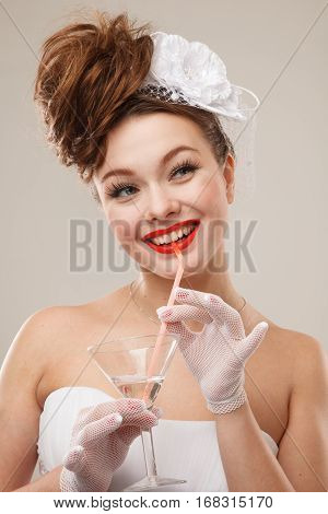 Excited Pin-up bride with glass of martini.Professional make-up hair and style.