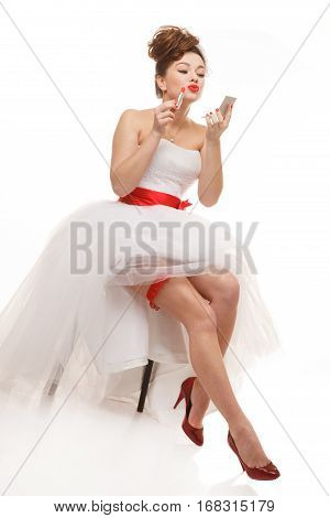 Excited Pin-up bride sits with lipstick and mirror.Professional make-up hair and style.Isolated on white