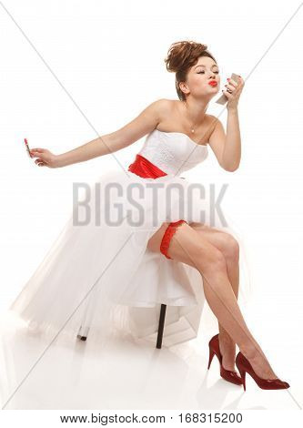 Pin-up bride sits with lipstick and mirror.Professional make-up hair and style.Isolated on white