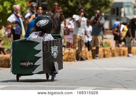 ATLANTA, GA - AUGUST 2016:  A girl steers her homemade car downhill in the Cool Dads Rock Soap Box Derby in the Old Fourth Ward in Atlanta GA on August 13 2016.