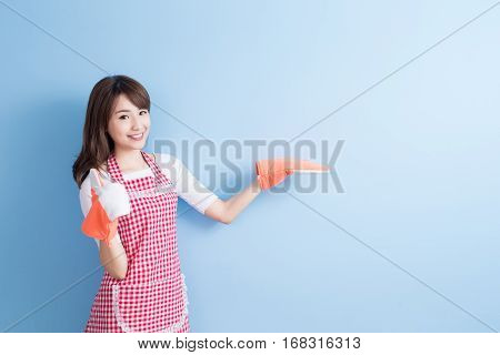 beauty housewife thumb up and wear gloves isolated on blue background