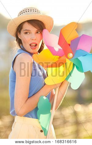 Young happy funny (vintage) dressed woman close-up  with colorful weather vane,looking like flower  Picture ideal for illustating woman magazines.