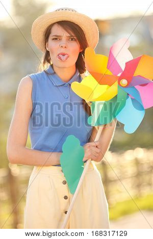 Young happy funny (vintage) dressed woman shows her tongue. With colorful weather vanelooking like flower Picture ideal for illustating woman magazines.