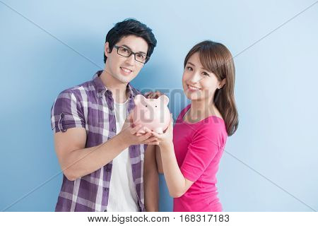 young couple hold pink pig bank and smile happily isolated on blue background
