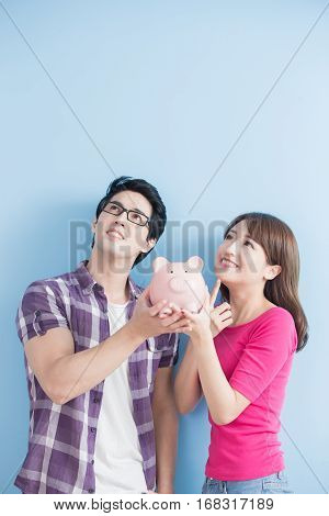young couple hold pink pig bank and look somewhere isolated on blue background