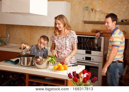 Family - motherfather and 7 year old son are cooking together in the kitchen