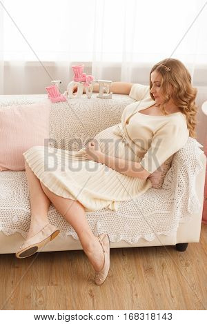 Pregnant blond woman sits on the couch at home with pink baby's bootees and love letter. Modern interiori pastel colors. Professional style and make-up