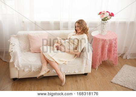 Pregnant blond woman sits on the couch at home and smles. Modern interiori pastel colors. Professional style and make-up