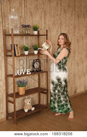 Pregnant blond woman in dress with peacock pattern stands with the waternig can near stand with flowers booksetc. Modern interior. Professional style and make-up