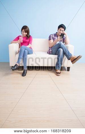 young couple look phone happily at home