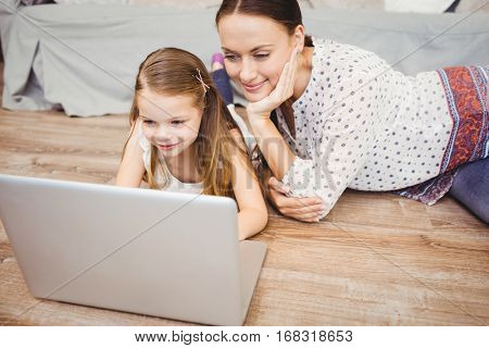 Smiling daughter using laptop with mother while lying on hardwood floor at home