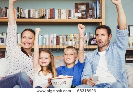 Cheerful family with arms raised while sitting on sofa at house