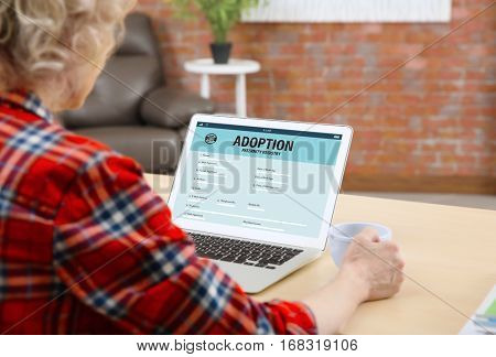 Adoption concept. Senior woman filling in paternity form on tablet
