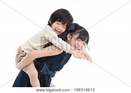 Asian girl giving her brother piggyback ride on white background isolated