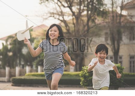 Cute Asian children playing cardboard airplane together in thee park outdoors