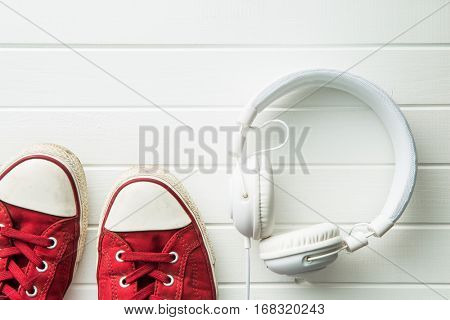 Red sneakers and headphones on white table.
