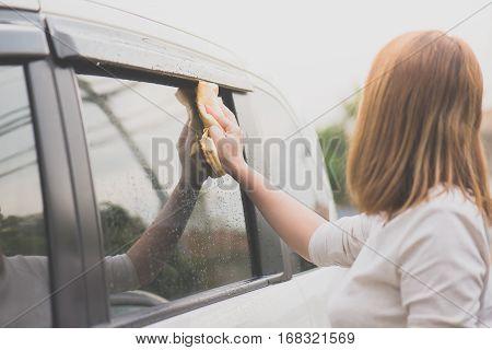 Asian woman washing car window with microfiber cloth
