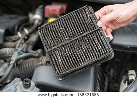 Technician holding dirty air filter for car
