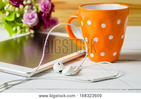 ear pods headphone tablet with orange cup of coffee on white wooden table