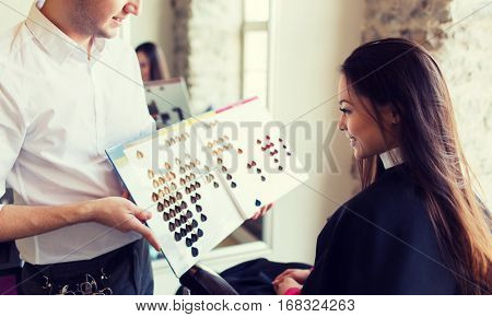 beauty, hair dyeing and people concept - happy young woman with hairdresser choosing hair color from palette samples at salon
