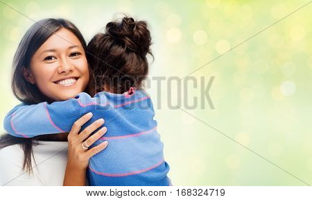 family, children, love and happy people concept - happy mother and daughter hugging over green holidays lights background