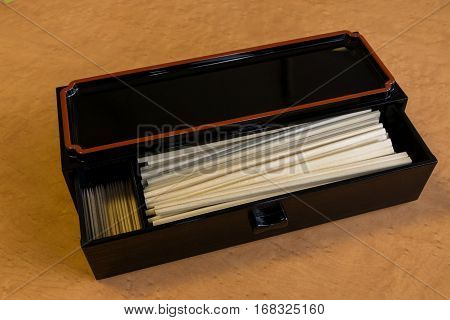 Chopsticks and toothpick in japanese style box with wooden table background.