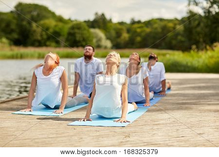 fitness, sport, yoga and healthy lifestyle concept - group of people making cobra pose on river or lake berth