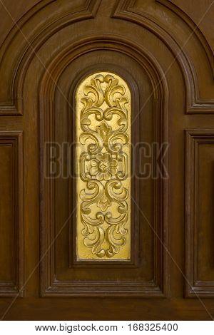 vintage teak wood door with gold carving.