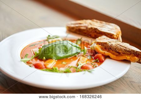 food, dinner, culinary, haute cuisine and cooking concept - close up of plate with delicious gazpacho soup and bread at restaurant