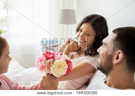 people, family, holidays and morning concept - happy little girl giving flowers to mother in bed at home