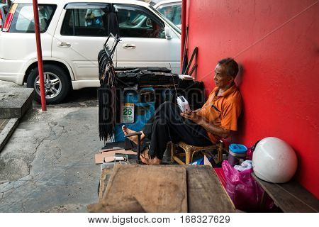 GEORGETOWN PENANG MALAYSIA - JANUARY 26 2017: A street cobbler shoe repairer. A man of Asian appearance sitting on street red wall repairing shoes of passers-by in the hands old radio receiver and antenna.