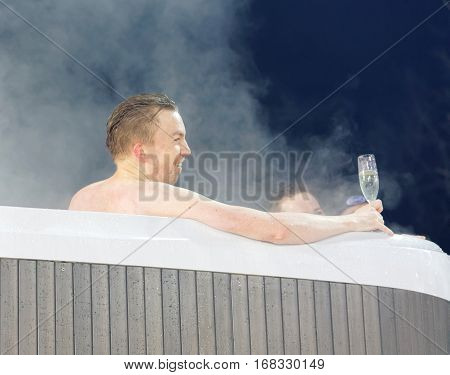 STOCKHOLM SWEDEN - JAN 31 2017: Man drinking champagne in a VIP hot tub at the Alpine Audi FIS Ski World Cup - city event January 31 2017 Stockholm Sweden