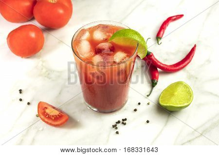 Bloody Mary cocktail on a white marble texture, with red hot chili peppers, slices of lime, tomatoes and copy space