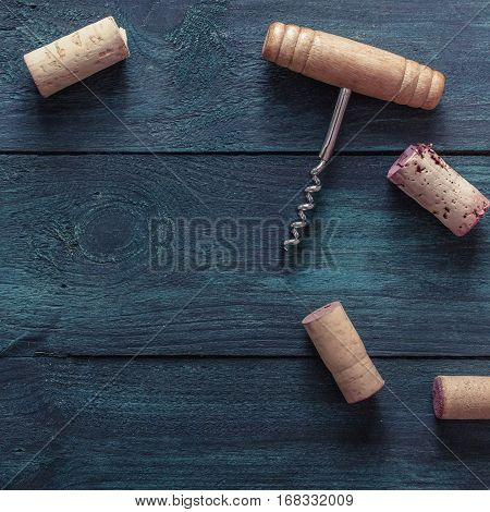 A square photo of an old-fashioned corkscrew with corks, shot from above on a dark blue background texture with copy space. A design template for a wine list or a tasting invitation