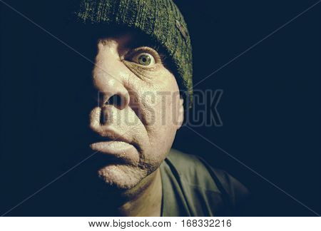 Toned low key portrait of a surprised man with wide eyes. His face lit up halfway.