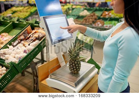 shopping, sale, consumerism and people concept - woman weighing pineapple on scale at grocery store