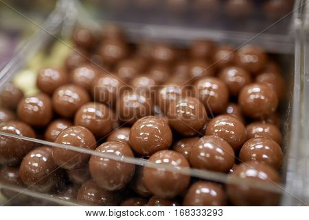 food, junk-food, confectionery and unhealthy eating concept - close up of chocolate dragee balls in transparent plastic box at candy shop