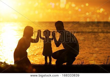 Silhouette of Asian family outdoor activity, enjoying holiday together on coastline in beautiful sunset during vacations.