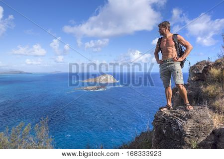 Muscular shirtless Caucasian man with toned abdominal muscles stands wearing backpack and cargo shorts on top of rocky mountain overlooking ocean and islands near Macapu'u Beach Oahu