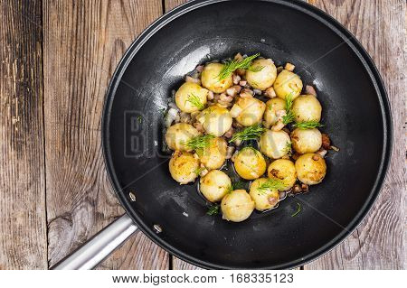Fried potato dumplings with bacon in frying pan. Studio Photo