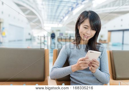 Woman using cellphone phone at departure hall of airport