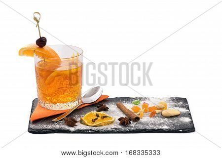 Orange coctail in the glass and beautiful serving dishes with cinnamon sticks, oranges and small candies in isolated white background close-up